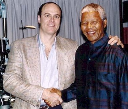 Richard Weiss, M.D. shakes hands with late former South African President Nelson Mandela.