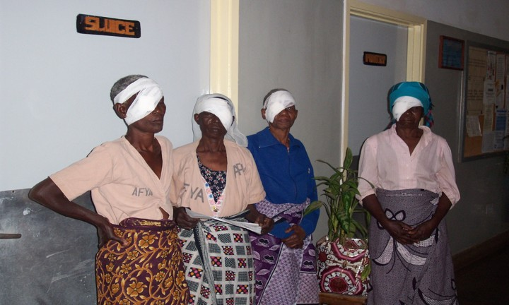 Four Tanzanian women wait post operatively, with bandages over one eye.